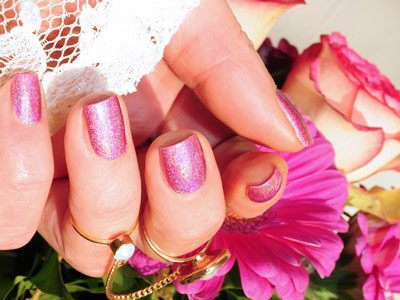 Beautifully painted nails on a hand holding a flower.